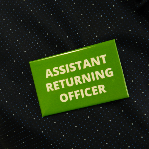 Assistant Returning Officer Badge printed in two colours on aluminum with safety pin back to quickly identify your team members on voting day.