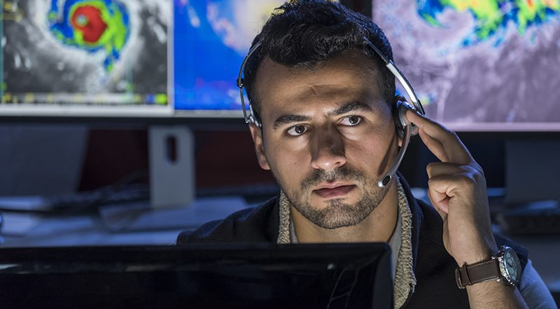 Meteorologist monitoring storms on his computer screens