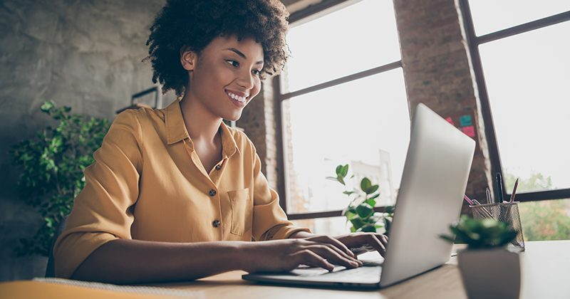 Photo of cheerful positive business lady smiling toothily looking into screen of notebook computer comparing corporate income for previous year with current one